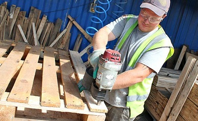 A man recycling a wooden pallet by re-strengthening it
